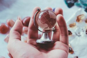 A person holding a small glass globe