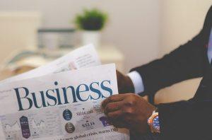 A businessman holding a business newspaper.