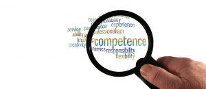 A person looking at the word competence through a magnifying glass.