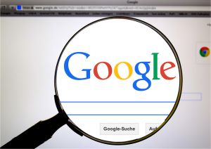 Magnifying glass showing Google search bar.