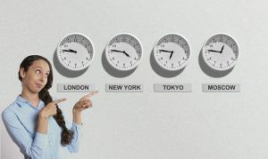 A woman pointing at clocks which are showing time in major cities in the world.