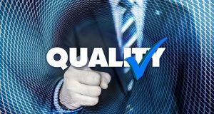 """A businessman pointing to the word """"quality""""."""