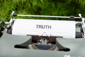 "A writing machine with a paper with ""Truth"" written on it."