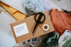 There is a parcel, and on the parcel there are scissors and tape.