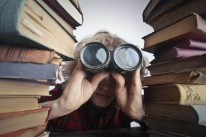 There is a person sticking out between two piles of books, holding binoculars.