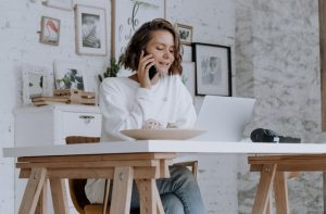 There is a woman sitting at the table, talking on the phone. Verifying your business via phone is the last step in setting up your GMB listing.