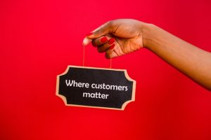 """A person is holding a signboard saying """"Where customers matter""""."""