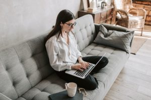 There is a person sitting on a sofa, typing something on a laptop. People nowadays search everything online, that's why NAP & user experience are crucial to local SEO.
