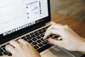 A person is typing on her laptop. If you want to find the authority sites in your niche, looking for the sites whose content is shared on a social network can be good tactics.