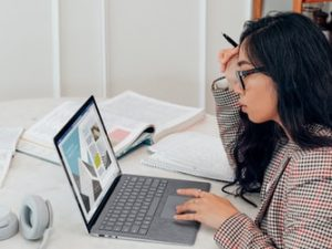 A woman sitting at a table and working on her laptop.