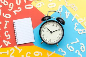There is a notebook and an alarm clock, and there are some numbers on a colorful background behind them.