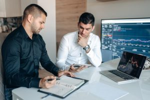 There are two men sitting at the table discussing some graphs. Doing good analysis is an important step that has an impact on how long it will take to see results from SEO.