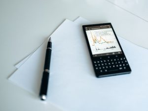 A phone with graphs next to blank papers and a pen.